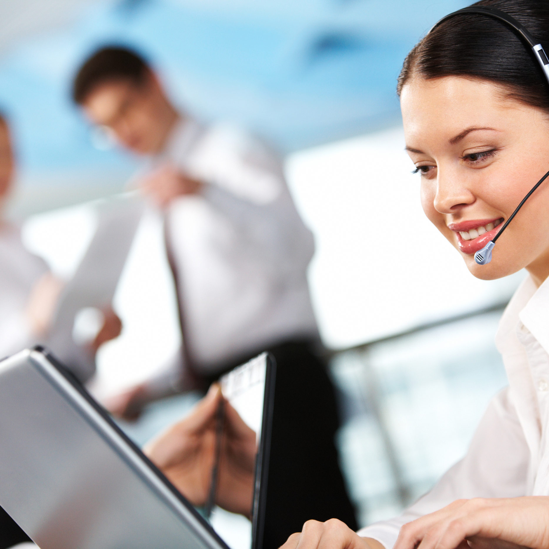Portrait of executive female in headset working on background of communicating partners